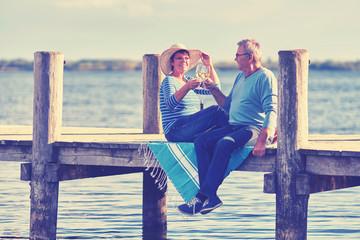 Senioren sitzen am See und trinken Wein