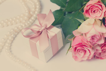 Gift box with pink ribbon and rose flowers on white table, retro toned