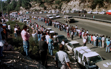 Hundreds of Israelis line the Tel Aviv to Jerusalem highway as the military vehicle carrying the cof..