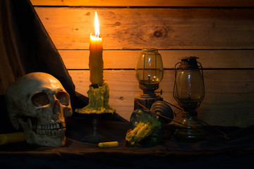 Skull with candles and barn lanterns on black cloth and old wooden wall