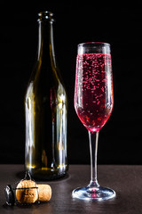 glass of pink sparkling champagne standing on a dark surface