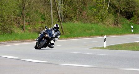 Kurvenlage, sportlicher Motorradfahrer legt sich in eine Linkskurve