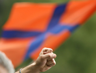 A protester raises a clenched fist with an opposition flag in the background during a rally in central Yerevan