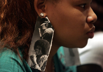 Bianca Rodwell wears earrings made from pictures of Jackson while watching a live television broadcast of the memorial service for Jackson in Detroit