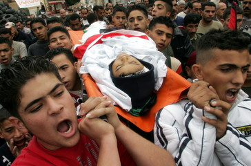 Palestinian teenagers carry the body of 13-year-old Palestinian boy Ahmad al Khateep during his fune..