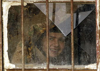 An Iraqi woman looks out of a window of her home in the city of Nassiriya on April 10, 2003. U.S. fo..