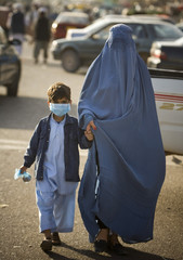 Afghan boy wearing a protective face mask walks with his mother along a street in Herat