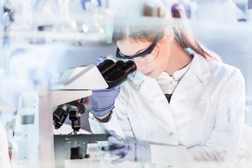 Life scientists researching in laboratory. Attractive female young scientist microscoping in their working environment. Healthcare and biotechnology.