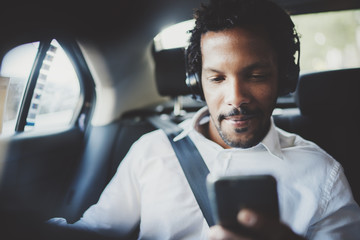Handsome african man listening music on smartphone while sitting on backseat in taxi car.Concept of happy young people traveling.Blurred background.