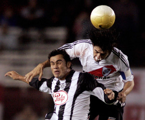 Caceres River Plate jumps for header over Gamarra of Libertad in Buenos Aires