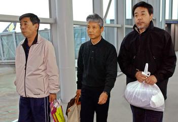 Captain Inoue, chairman Kanji and chief engineer Kuroda walk upon their arrival at the Incheon ...
