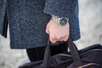 мужская рука с часами держит сумку