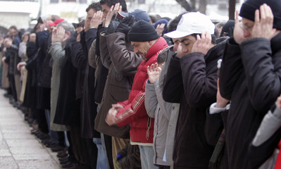 Bosnian Muslims pray outside a mosque in the old part of Sarajevo