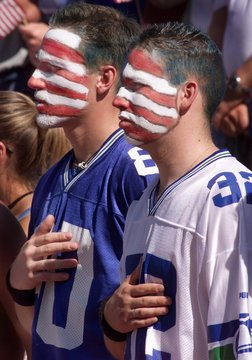 PATRIOTIC SEAHAWKS FANS WEAR PAINTED AMERICAN FLAGS ON THEIR FACES.