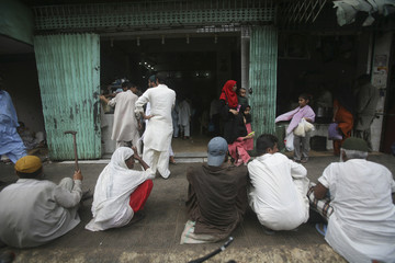 People wait to get free food outside a hotel in Karachi