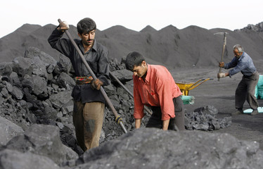 Kurdish workers shovel coal at a roadside coal shop in the southeastern Turkish province of Sirnak
