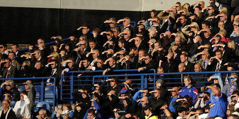 Rangers' supporters shield their eyes during their team's Scottish Premier League soccer match against Aberdeen at Ibrox Stadium in Glasgow