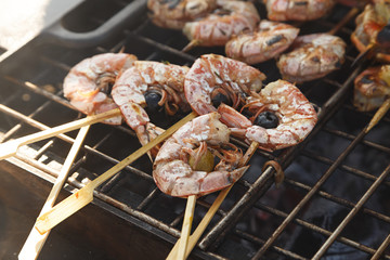 Cooked prawns on skewers with olives