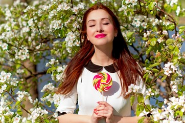 Sweet American red-haired girl with colored caramel candy in her hand. Woman in the garden next to blooming white trees in a white dress with a collar