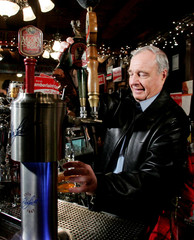 Canadian PM Martin pours a draft beer during a campaign stop at a pub in Guelph