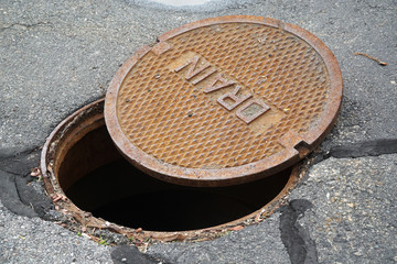 close up on opened rustic manhole cover on the street
