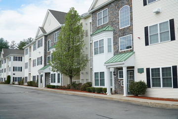 rental apartment buildings in a row with spring tree