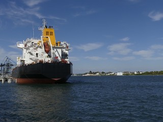 Products Tanker ship discharging at the Oil Terminal of Lorient, France, with black hull and yellow funnel on a sunny day. Horizontal stern view