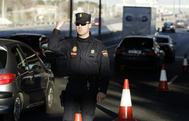A Spanish civil guard directs traffic on the A2 motorway near one of the blast sites in Madrid