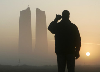 A journalist takes a photograph of the Canadian National Vimy Memorial at sunrise in Vimy