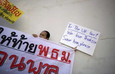 A pro-government supporter holds signs while rallying with tens of thousands at Rajamangala Stadium in Bangkok