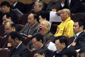 A delegate yawns as China's Supreme People's Court President Xiao Yang delivers a work report in Beijing