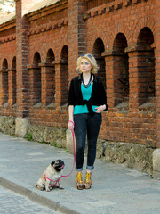 Pretty blonde girl walking with funny pug. Funny dog with tongue hanging out near brick wall on the sidewalk