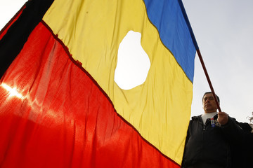 A man holds the national flag during a religious service for the victims of Romania's 1989 anti-communist revolt in Timisoara
