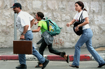 A PALESTINIAN FAMILY RUNS TO SAFTY IN THE WEST BANK TOWN OF BEIT JALA.