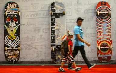 Attendees walk past larger than life skateboard images at the Action Sports Retailers show in San Diego Diego