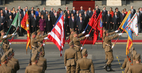Hungarian soldiers present flags to a foreign delegation in front of the parliament building in Budapest