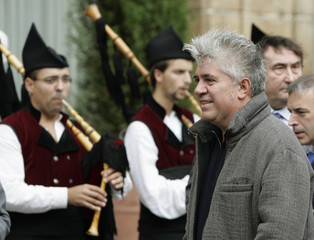 Director Pedro Almodovar walks near pipers dressed in traditional costumes of Asturias in Oviedo