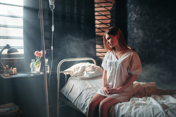 Young sick woman sitting on hospital bed on drip