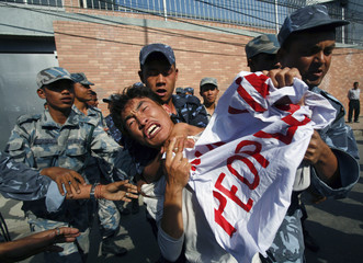 Policemen stop a Tibetan demonstrator as he attempts to reach the gate of the Chinese Embassy Visa Section in Kathmandu