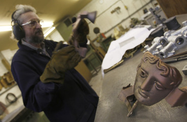 A worker at New Pro Foundries fettles a bronze BAFTA mask in west London