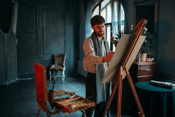Male painter with brush in front of easel