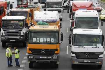 Two truck drivers talk beside a truck along A1 motorway in Madrid