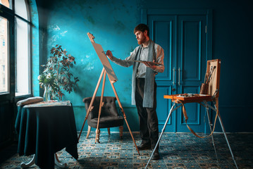 Artist with palette and brush paint on easel