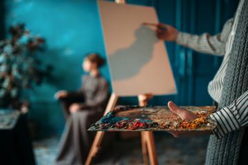 Male painter paints womans portrait