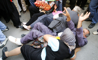 People fall while trying to get eggs and potatoes distributed by Bosnian farmers in front of the Constitutional Court in central Sarajevo
