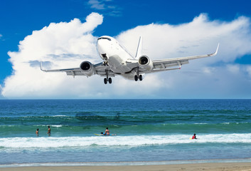 Passenger plane flies over the beach with people on the ocean coast