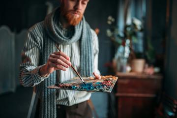Artist paints colors on the palette, art studio