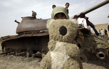 A girl shows her teddy bear in front a destroyed Russian tank in the stronghold village of Panjwaii, Kandahar province