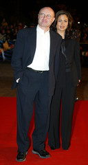 British singer Phill Collins arrives with an undentified woman at the Cannes festival palace in Cann..