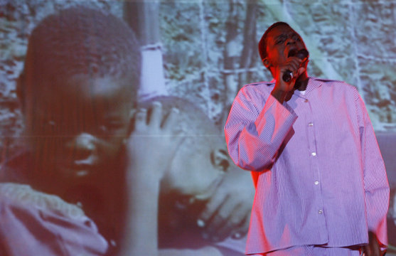 A Zimbabwean artist sings in front of a projected background during the main act of the opening day of the Harare International Festival of the Arts